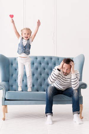 I can do everything. Joyful active naughty child standing on the sofa and holding her arms up while being in a great mood