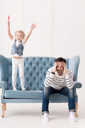 upbringing: Problems with upbringing. Pensive sad depressed father holding his head and looking at you while having some problems with his daughter upbringing