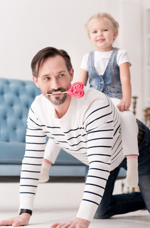 Entertainment for children. Good looking positive brunette man grabbling and holding a candy in his teeth while playing with his daughter