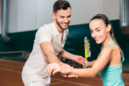 learning process: Learning process. Positive bearded professional instructor teaching young slim beautiful woman to play tennis while having a lesson in an indoor tennis court Stock Photo