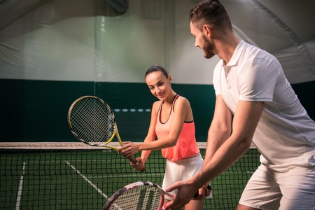Learn with pleasure. Positive delighted beautiful woman holding racket and learning to play tennis with professional instructror in indoor tennis court