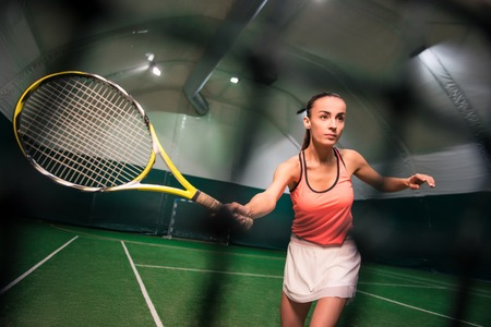 Pleasant charming serious woman playing tennis while training in the indoor tennis court