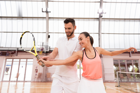 Just here. Positive professional instructor showing young woamn how to hold racket while teachign to play tennis Stock Photo