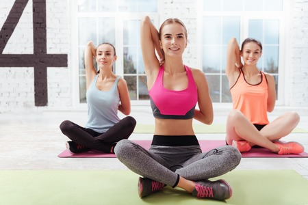 asanas: Three happy young women doing asanas while having yoga class and spending time in a gym. Stock Photo