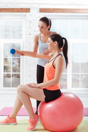 fitball: Two athletic young women training while using fitball and dumbbells and spending time in a gym.