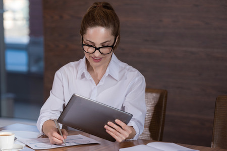 workday: Beautiful young ambitious woman working hard on project while sitting in the office and using tablet. Stock Photo