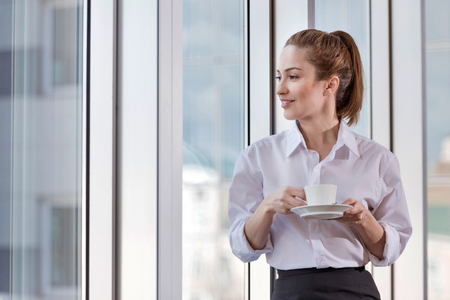 Pretty young delighted woman enjoying coffee break while spending time at her workplace and relaxing.