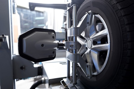 Close up of car tyre fixed in alignment machine clap while being checked