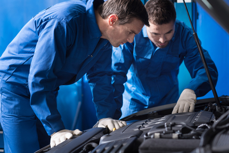 break out: Professional serious mechanics examining car engine and repairing break out while working in auto service