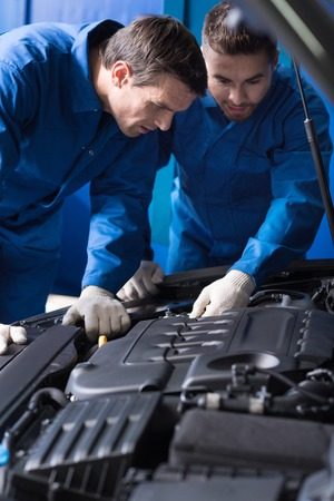 break out: Concentrated experienced, mechanics talking and discussing break out while repairing car engine