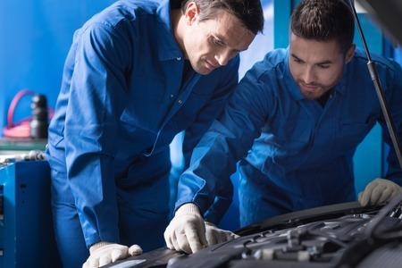 break out: Serious experienced mechanics discussing break out while repairing car engine Stock Photo
