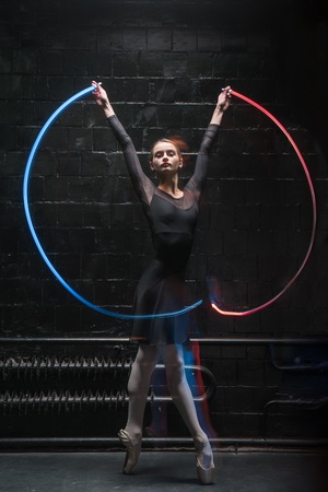 I enjoy ballet. Charismatic graceful young ballet dancer standing in front of the dark wall on tiptoe while raising her hands and holding the colorful gymnastic ribbon Stok Fotoğraf