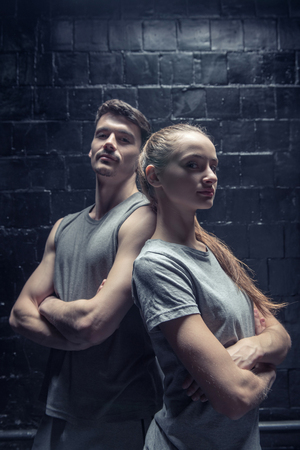 Pleasant young dancers standing near the black wall while expressing concentration and standing back to back with crossed arms