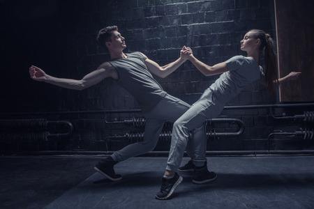 persistent: Involved persistent young dancers performing near the black wall while expressing concentration and interaction in the dancing hall
