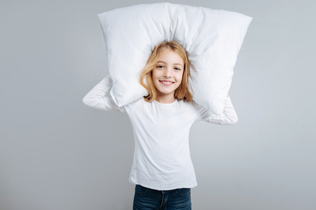 Joyful delighted little girl holding pillow and smiling while standing isolated on grey background