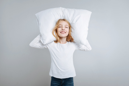Pleasant content little girl closing her eyes and holding her head on the pillow while resting Stock Photo
