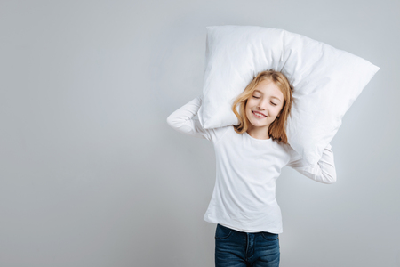 Cheerful content cute little girl holding pillow and going to sleep while standing isolated on grey background