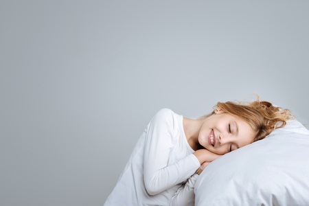 Positive cute little girl closing her eyes and lying on the pillow while pretending to sleep