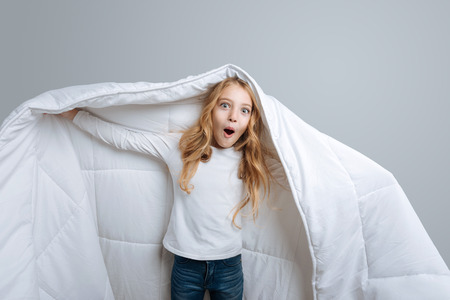 Pleasant emotional little girl covering with blanket and expressing positivity while standing isolated on grey background