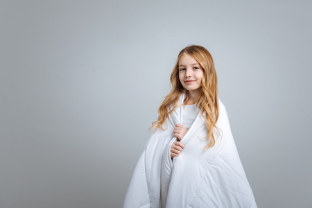 Positive nice little girl covering with blanket and smiling while standing isolated on grey background Stock Photo