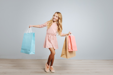 Pleasant cute little girl smiling and holding shopping bags while standing isolated n grey background