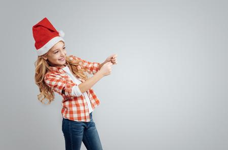flapper: contenido positivo niña sonriente y la celebración de la aleta, mientras que de pie aislado en fondo gris Foto de archivo