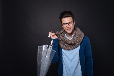 manhood: Cheerful content handsome man holding umbrella and smiling while standing on black background Stock Photo