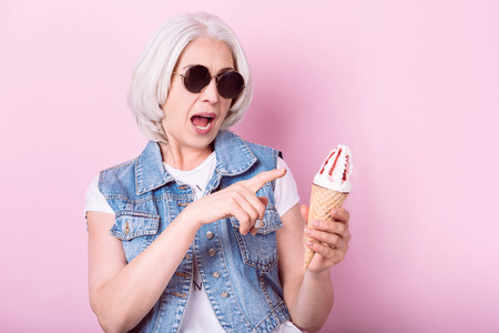 My favorite icecream. Expressive senior pretty woman opening her mouth and pointing on icecrem in her hand while standing against isolated pink background.