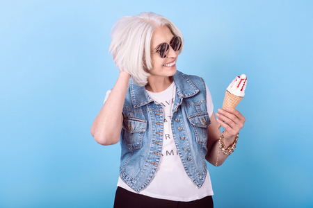 Want something sweet. Joyful senior pretty woman smiling and holding an icecream while standing against isolated blue background. Stock Photo