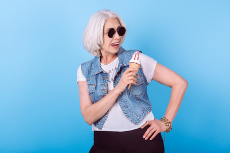 filings: Funny lady. Emotional pretty senior woman licking lips and holding an icecream while standing against blue isolated background.