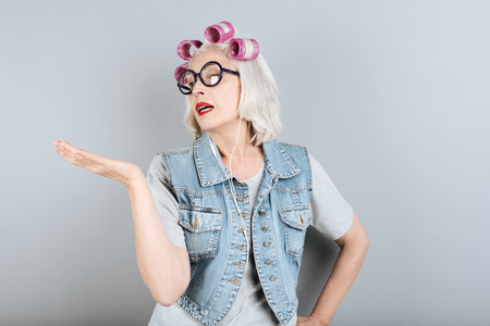 Goodbye sadness. Emotional senior beautiful woman gesturing and using headphones while standing against isolated gray background.