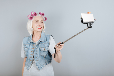 overjoyed: Good idea. Overjoyed senior beautiful woman smiling and taking selfie while standing against isolated gray background.