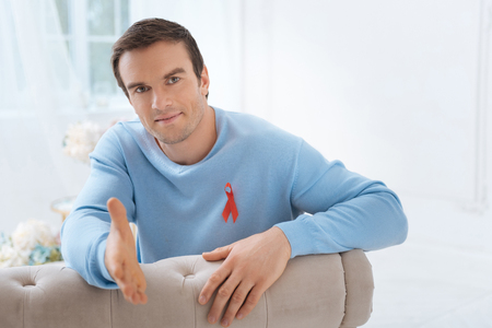 My greetings. Handsome positive young man sitting on the sofa and giving you his hand while wearing a red ribbon