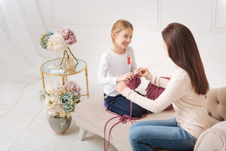Appreciate the moment. Happy nice young mother looking at her daughter and teaching her to knit while spending time with her Stock Photo