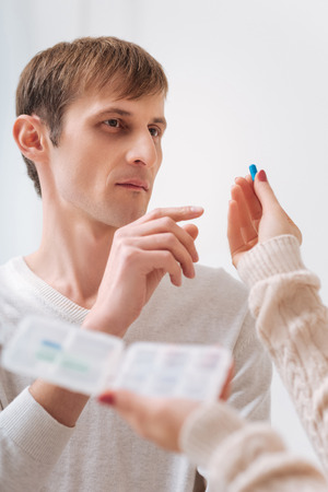 Serious illness. Unhappy thoughtful young man taking a pill and looking at it while taking medicine