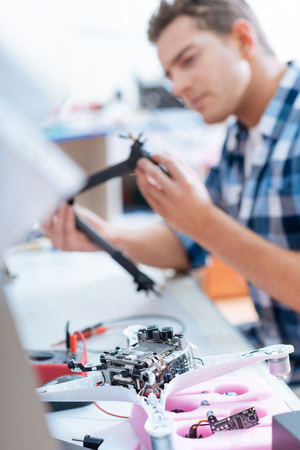 Save it. Handsome young concentrated man repairing drone detail and sitting at his workplace while working as a repairman. Stock Photo