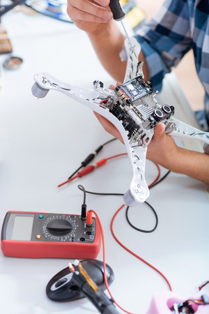 Hard process. Close up of a young handsome concentrated man repairing drone detail while holding screwdriver and using electronic tester. Stock Photo