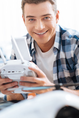 Happy young handsome man holding drone remote controller while using mechanism and smiling.