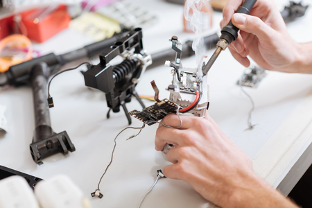 Patience and energy. Detailed close up of mans hands soldering drone chips while using soldering iron while sitting in a workroom. Stock Photo
