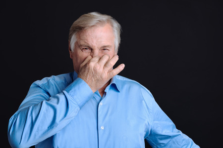Feeling that unpleasant smell. Elderly man keeping his fingers on nose plugs looking at camera with disgust because of stink smell Stock Photo