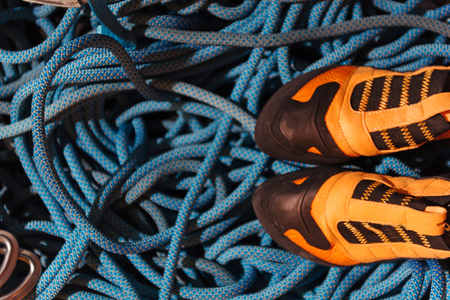 Good equipment. Close up of orange climbing boots standing on blue insurance ropes.