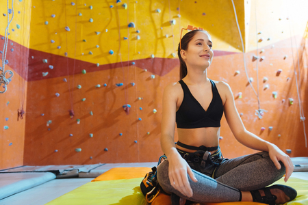 waiting posture: Concentrated on it. Pretty young delighted woman sitting in a lotus posture in climbing gym while waiting for training and smiling.