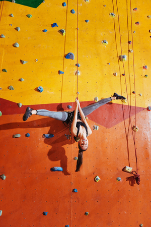 Love extreme. Active young delighted woman making a trick on a climbing wall while training and wearing sportswear and special equipment. Reklamní fotografie