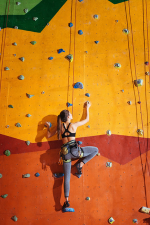 Conquer it. Pretty young active woman climbing up the orange wall in gym while training and wearing sportswear and special equipment Stock Photo
