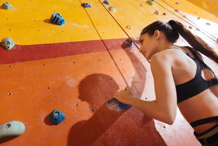 Want more. Young beautiful active woman climbing up the wall in gym while training and wearing sportswear and special equipment