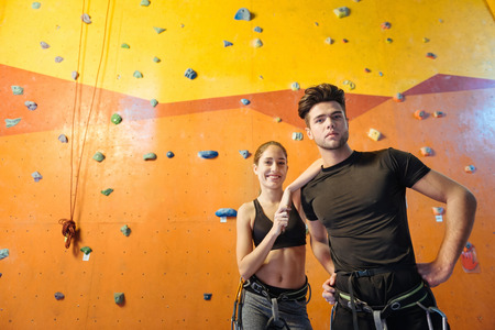 Having fun. Joyful active young man and woman posing while standing in climbing gym and preparing to training.