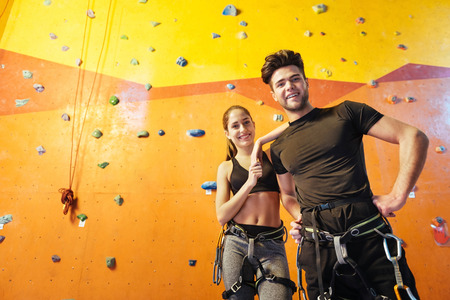 overjoyed: Happy together. Overjoyed active young man and woman posing while standing in climbing gym and preparing to training.