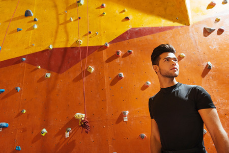 Sport and style. Young active confident man standing near climbing wall while posing in climbing gym and smiling.