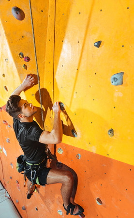 overjoyed: Strength and dexterity. Overjoyed confident young man spending time in climbing gym while climbing up the wall and using equipment.