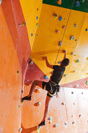 Do it right now. Active young delighted man training hard in climbing gym while using equipment and climbing up the wall.